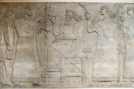 enthroned: LONDON, UNITED KINGDOM - JUNE 5, 2014: British Museum. King Ashurnasirpal is enthroned between attendants. Assyrian, about 865-860 BC Editorial