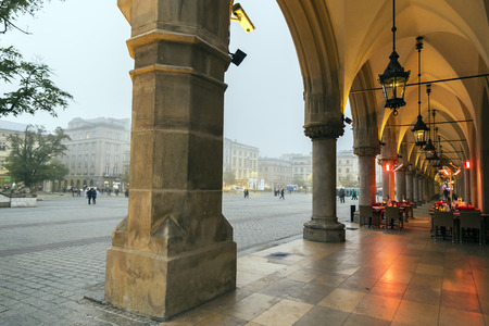 arcades: KRAKOW, POLAND - OCTOBER 26, 2014: Cafe located under the arcades of Sukiennice the Cloth Hall by evening. Editorial