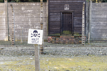 elektrischer Zaun: AUSCHWITZ, POLAND - OCTOBER 25, 2014: Warning sign in front of an electric fence in the concentration camp of Auschwitz Editorial
