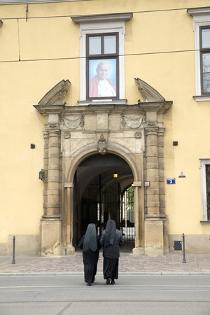 pope: KRAKOW, POLAND - OCTOBER 26, 2014: Two nuns walk into a religious residence. On the door a large photo of the Polish Pope John Paul II