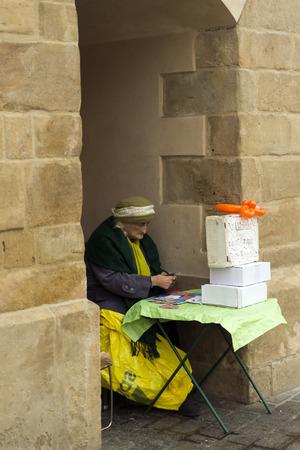 soothsayer: CRACOVIA, Polonia - 26 de octubre 2014: Un adivino ancianos espera clientes mientras baraja las cartas en la Plaza del Mercado