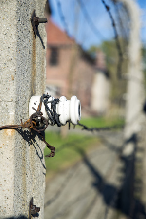 auschwitz: AUSCHWITZ, POLAND - OCTOBER 25, 2014: Warning sign in front of an electric fence in the concentration camp of Auschwitz Editorial