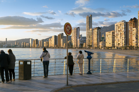 reputed: BENIDORM, SPAIN, JANUARY 20, 2015: tourists enjoy a warm winter day from Benidorms landmark ocean viewpoint. Benidorm is Spains Nr. 1 beach resort, reputed for its sunny climate all year round.