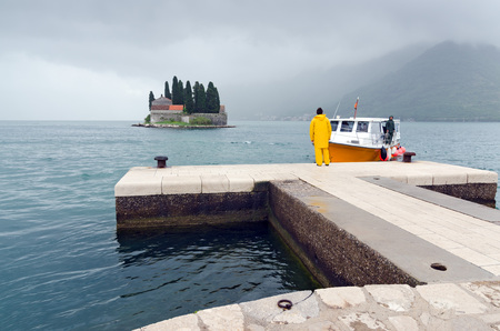 lady s: KOTOR'S BAY, MONTENEGRO - MAY 17, 2013: A sailor, wearing a yellow raincoat, waiting on the dock of island of Our Lady of the Rocks, the arrival of the boat that connects the small island to the mainland. On May 17, 2013, in Kotor's Bay, Montenegro