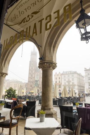 arcades: KRAKOW, POLAND - OCTOBER 27, 2014: Cafe located under the arcades of Sukiennice the Cloth Hall. Across is the Mariacki church.