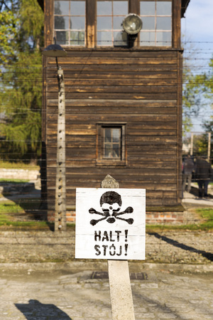 electric fence: AUSCHWITZ, POLAND - OCTOBER 25, 2014: Warning sign in front of an electric fence in the concentration camp of Auschwitz Editorial