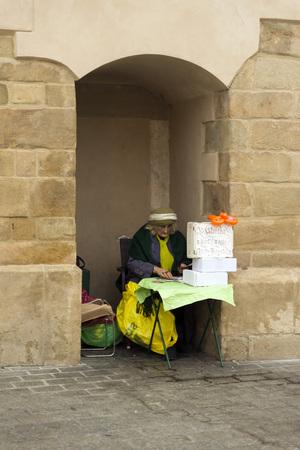 adivino: CRACOVIA, Polonia - 26 de octubre 2014: Un adivino ancianos espera clientes mientras baraja las cartas en la Plaza del Mercado