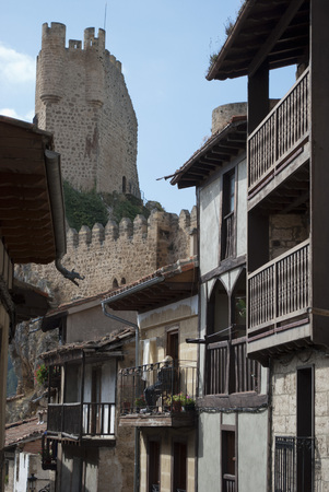 feudalism: FRIAS, BURGOS, SPAIN - OCTOBER 10, 1010: A neighbor on the balcony of his house in an alley in front of the castle, in Frias, Burgos, Spain, on October 10, 2010