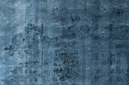 crazed: Blue  paint on an exterior wall cracked and flaking to reveal old concrete beneath Stock Photo