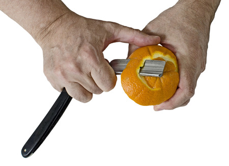 inappropriate: Peeling an orange with a razor. Isolated on white background Stock Photo