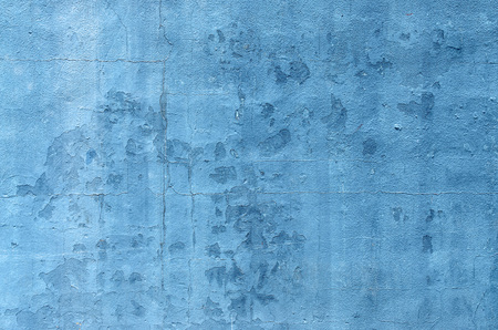 descriptive color: Blue  paint on an exterior wall cracked and flaking to reveal old concrete beneath Stock Photo