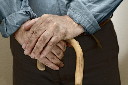 campesino: Peasant hands, leaning on a cane placed in front of him Foto de archivo