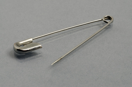 acute angle: Open Safety pin on gray background
