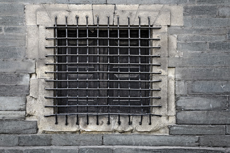 man made structure: barred window in a stone wall Stock Photo