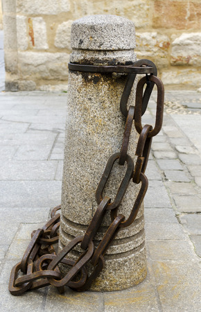 toughness: A strong metal chain attached to a bollard, at a quayside.