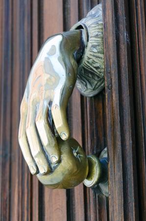 door knocker: A solid brass door knocker shaped as a hand holding an apple. Taken in Avila, Spain.
