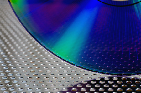 optical disk: Closeup of CD on a perforated metal surface