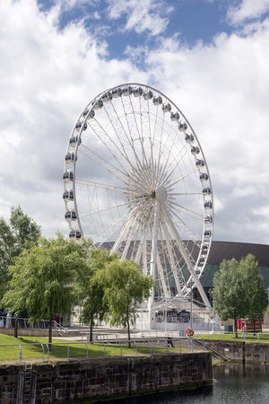 conditioned: The Wheel of Liverpool ferris wheel is shown on a blue sky day. The wheel includes 42 enclosed, air conditioned capsules.