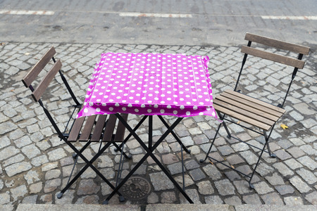 folding: two folding chairs and a folding table with pink tablecloth