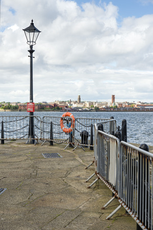 mersey: Street lights along the pier-head alongside the River Mersey as it runs through the city of Liverpool. Docks can be seen on the opposite side of the river. Stock Photo