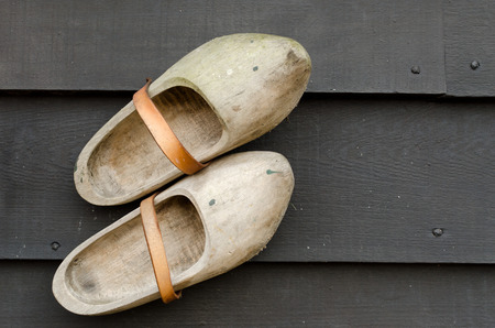 klompen: pair of traditional Dutch yellow wooden shoes on a wooden black table