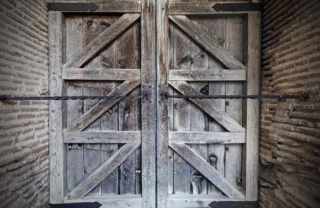 rejas de hierro: Vieja puerta de madera reforzada con barras de hierro
