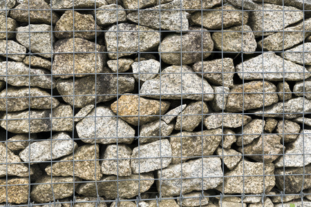 gabion: A huge Gabion Wall used as a fence on a slope. Colorful stones ideal for various kinds of backgrounds. Stock Photo