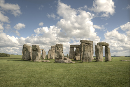 White fluffy clouds floating in a blue sky over the Stonehenge, Wiltshire Stock Photo