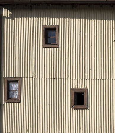 marginal: Three small windows in a corrugated iron wall in a slum.