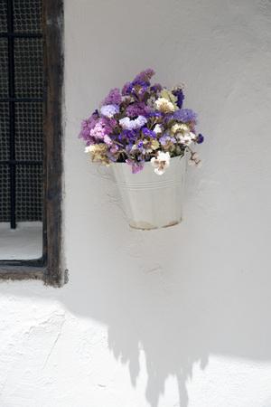 flores secas: Crisol blanco con flores secas en una pared de Ibiza