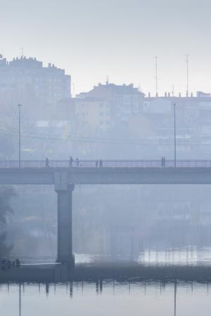 pedestrians: Pedestrians crossing a bridge on a bleak winter morning