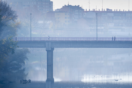 dreary: Pedestrians crossing a bridge on a bleak winter morning