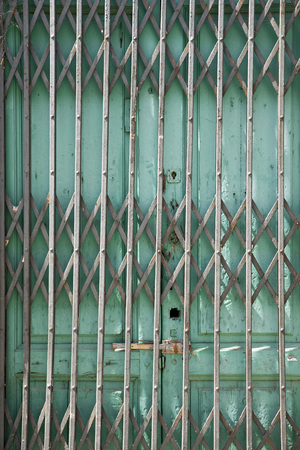 security shutters: Folding old metal door gate of abandoned store Stock Photo