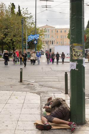 syntagma: ATHENS, GREECE - OCTOBER 31, 2015: Beggar asleep on Syntagma Square, facing the Greek Parliament