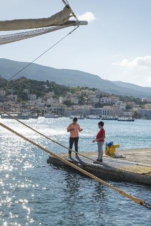 poros: POROS, GREECE-OCTOBER 25, 2015: Two boys fish on the pier of the island