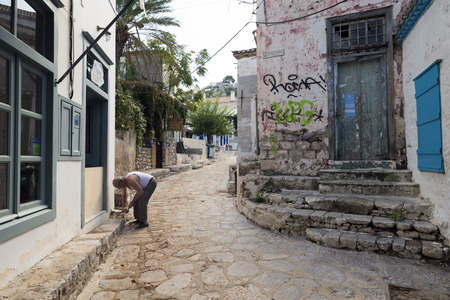 old man: HYDRA, GREECE - OCTOBER 25, 2015: A man repairs the sidewalk of a street in Hydra, an island in Greece