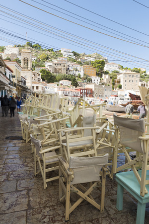 tidal wave: HYDRA ISLAND, GREECE - OCTOBER 25, 2015: Deck chairs restaurant stacked for cleaning after high tide Editorial