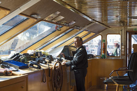 maneuvering: HYDRA ISLAND, GREECE - OCTOBER 25, 2015: Pilot on the bridge of a cruise ship maneuvering to dock
