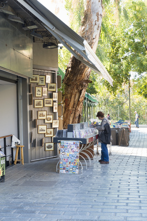 rummage: ATHENS, GREECE - OCTOBER 27, 2015: Thrift stores in the Plaka district. A man searches the DVD