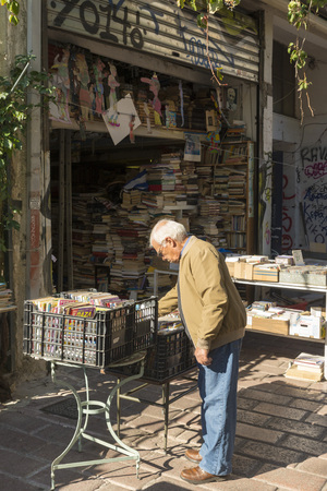 thrift: ATHENS, GREECE - OCTOBER 27, 2015: Thrift stores in the Plaka district. A man searches the CD