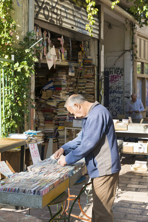 old man: ATHENS, GREECE - OCTOBER 27, 2015: Thrift stores in the Plaka district. A man searches the CD