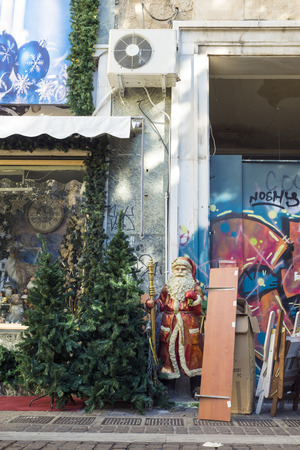 heterogeneous: ATHENS, GREECE - OCTOBER 27, 2015: Santa Claus and Christmas tree among other things to the door of a shop