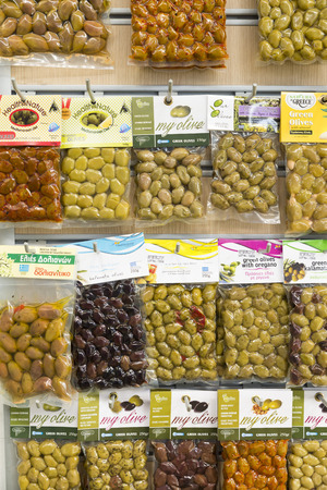 grocer: ATHENS, GREECE - OCTOBER 27, 2015: Many varieties of olives packaged for sale in a food shop in the Plaka district Editorial