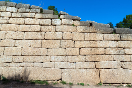 characterized: Cyclopean wall of The Treasury of Atreus or Tomb of Agamemnon at ancient Mycenae characterized by the use of massive stones of irregular shape and size of passage