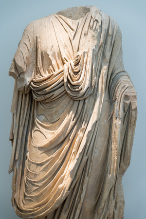 toga: OLYMPIA, GREECE - OCTOBER 29, 2015:  Statue of a man wearing a toga at Archaeological Museum of Olympia. Bronze lion head Editorial