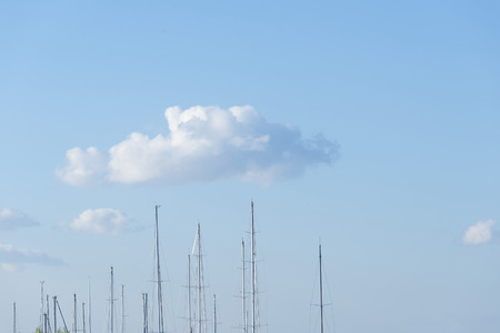 masts: Some sailboat masts on a blue sky with clouds background. Copy space