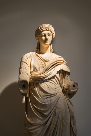 toga: OLYMPIA, GREECE - OCTOBER 29, 2015:  Statue of a woman wearing a toga at Archaeological Museum of Olympia. Bronze lion head Editorial