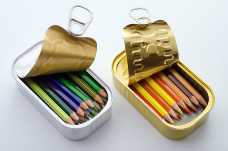 sardine can: Arrangement of two sardine tins filled with neatly sorted colored pencils on white background.