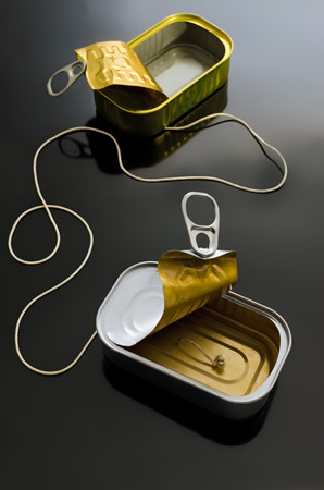 poorly: Two cans (poorly suited). One cord. One of the most well-known metaphors for communication. Or incommunication? Stock Photo