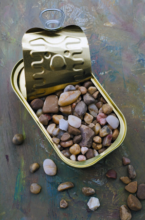 malnutrition: tin container filled with stones on wooden background
